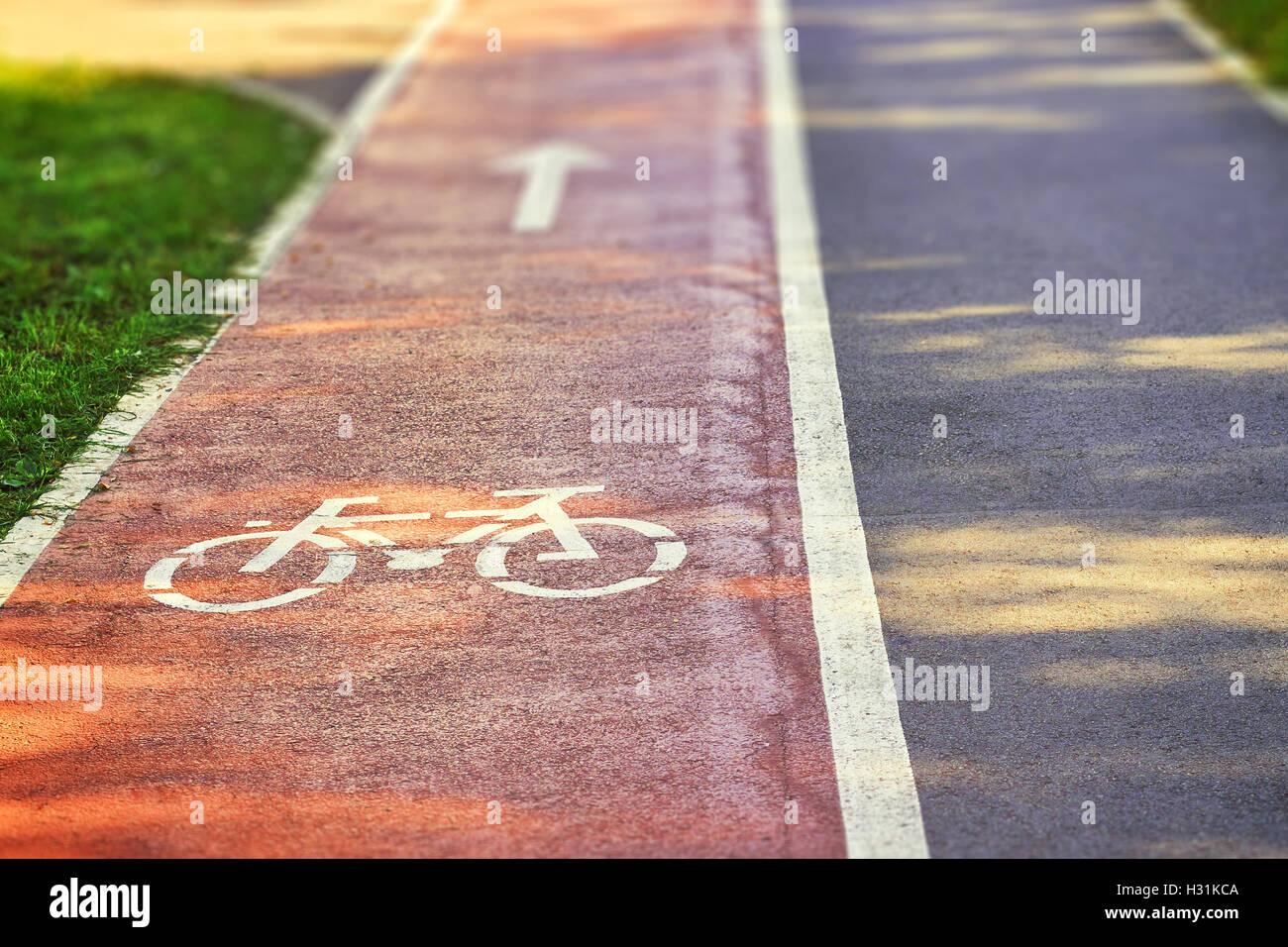 Roten Radweg auf Bürgersteig mit gemalten weißen Pfeil und Fahrrad schildern. Textfreiraum Stockfoto