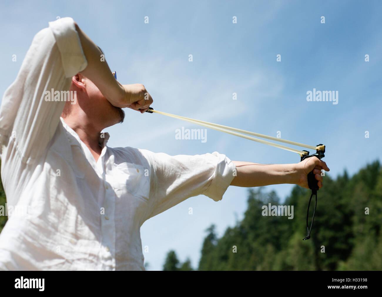 Ein Mann schießen ein Sling shot Stockbild