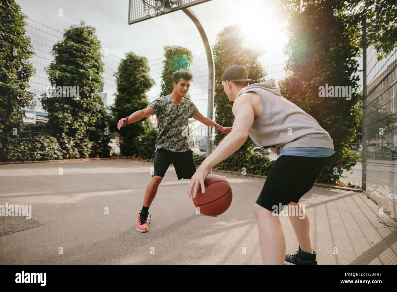 Junge Freunde zusammen zu spielen Basketball, junge vor Netto blockieren und andere dribbling den Ball auf Freiplatz. Stockbild