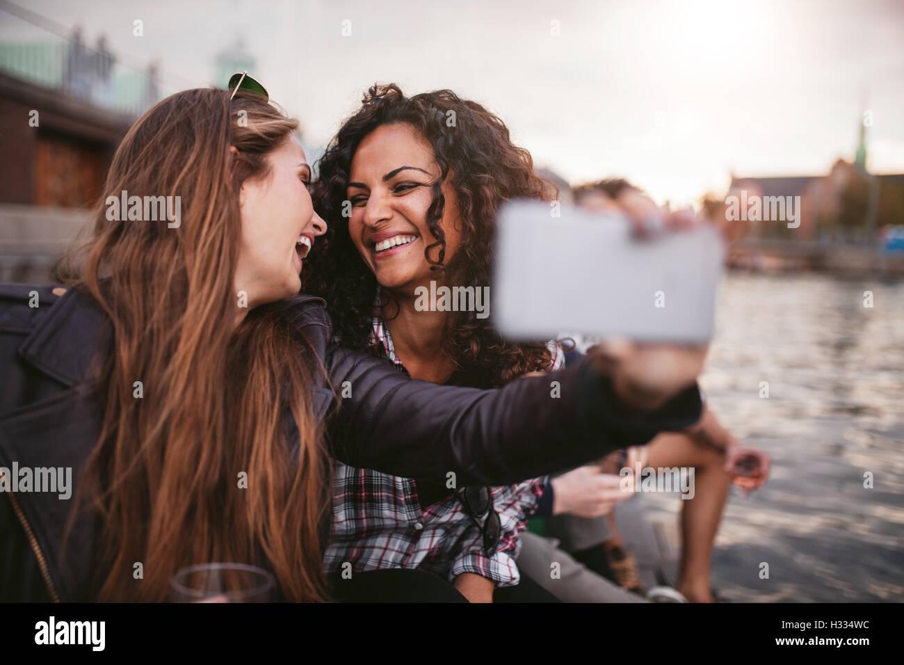 Fröhliche junge Frauen Freunde nehmen Selfie am See. Beste Freunde, die gemeinsam Spaß haben. Stockbild