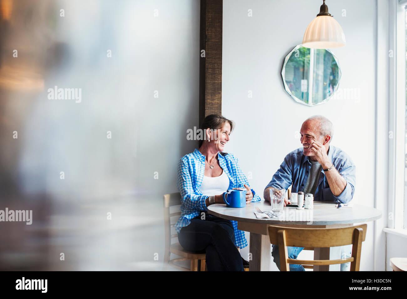 Zwei Menschen sitzen an einem Café-Tisch.  Unscharfen Vordergrund. Stockbild