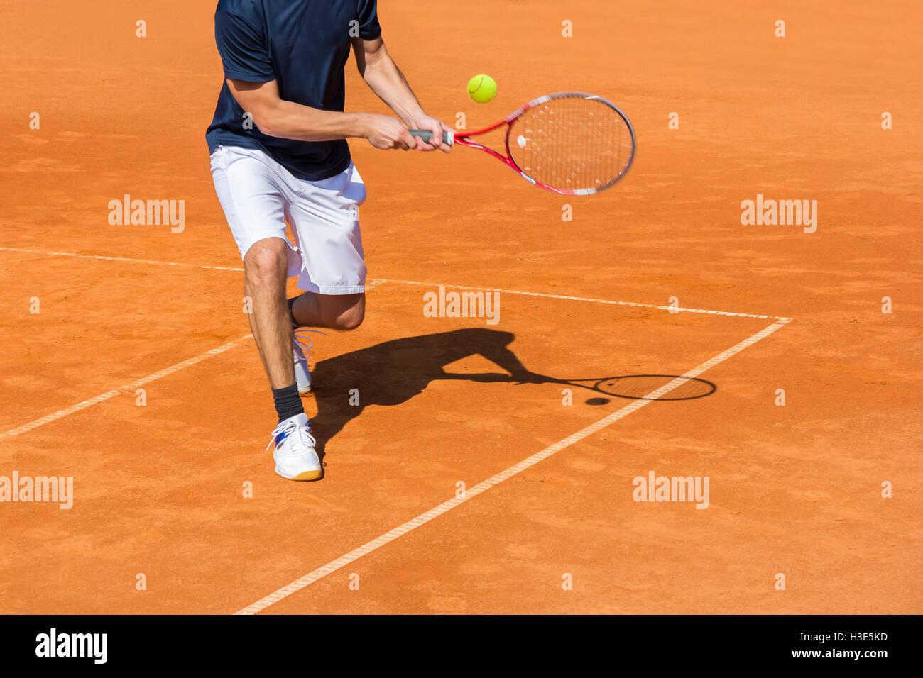 Tennisspieler in Aktion auf dem Sandplatz an einem sonnigen Tag Stockfoto