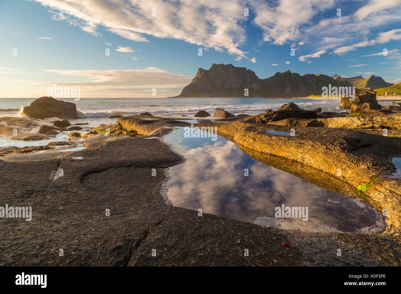 Felsen im Abendlicht mit warmen Licht auf sie mit Himmel reflektiert in einem Wasserbecken, hohen Bergen im Hintergrund, Stockbild