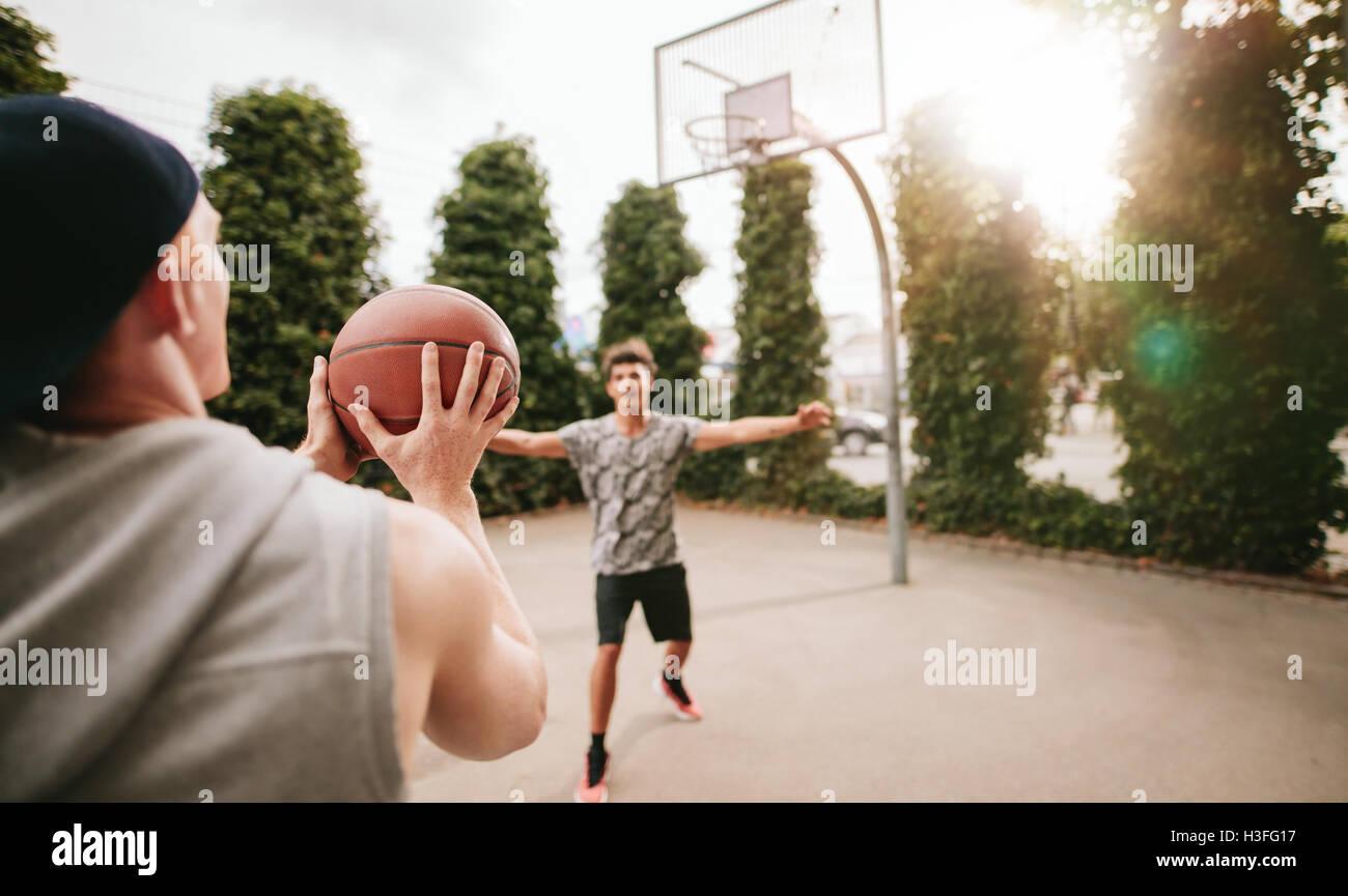 Junger Mann unter Schuss mit Freund blockieren am Basketballplatz. Streetball Spieler auf Platz Basketball zu spielen. Stockbild