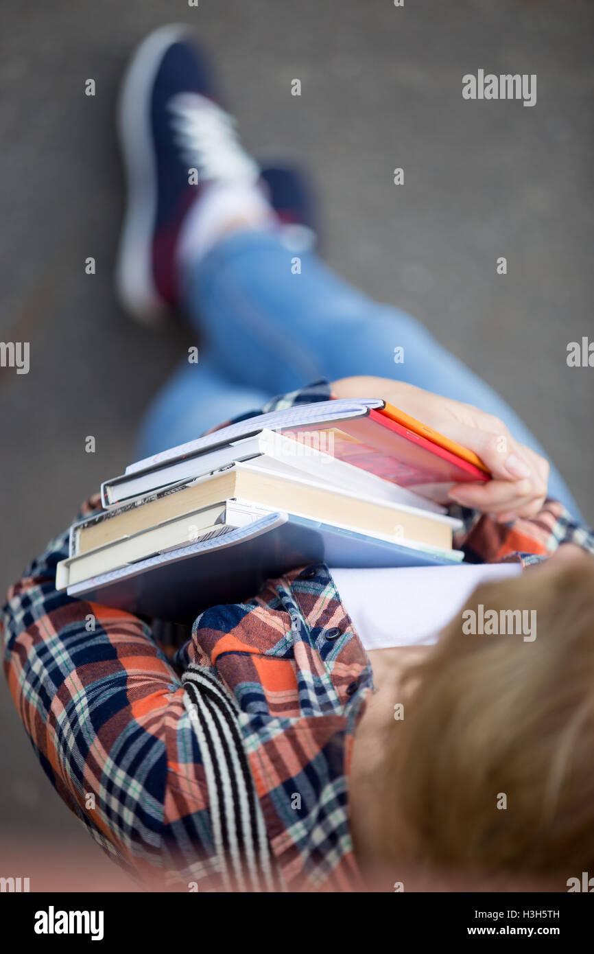 Studentin mit einem Haufen von Lehrbüchern und notebooks Stockbild