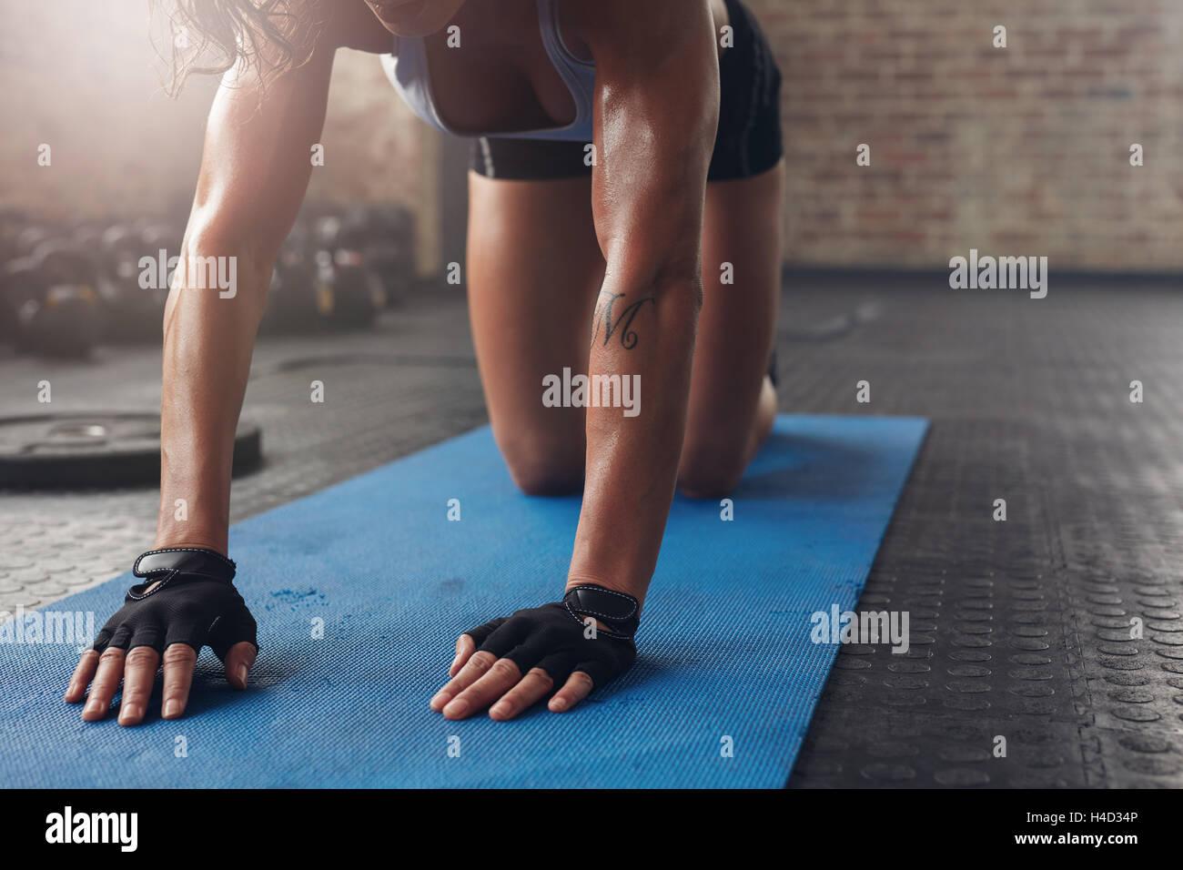 Weibchen auf Gymnastikmatte stretching Training zu tun. Konzentrieren Sie sich auf die Hand einer Frau auf Fitness Stockbild