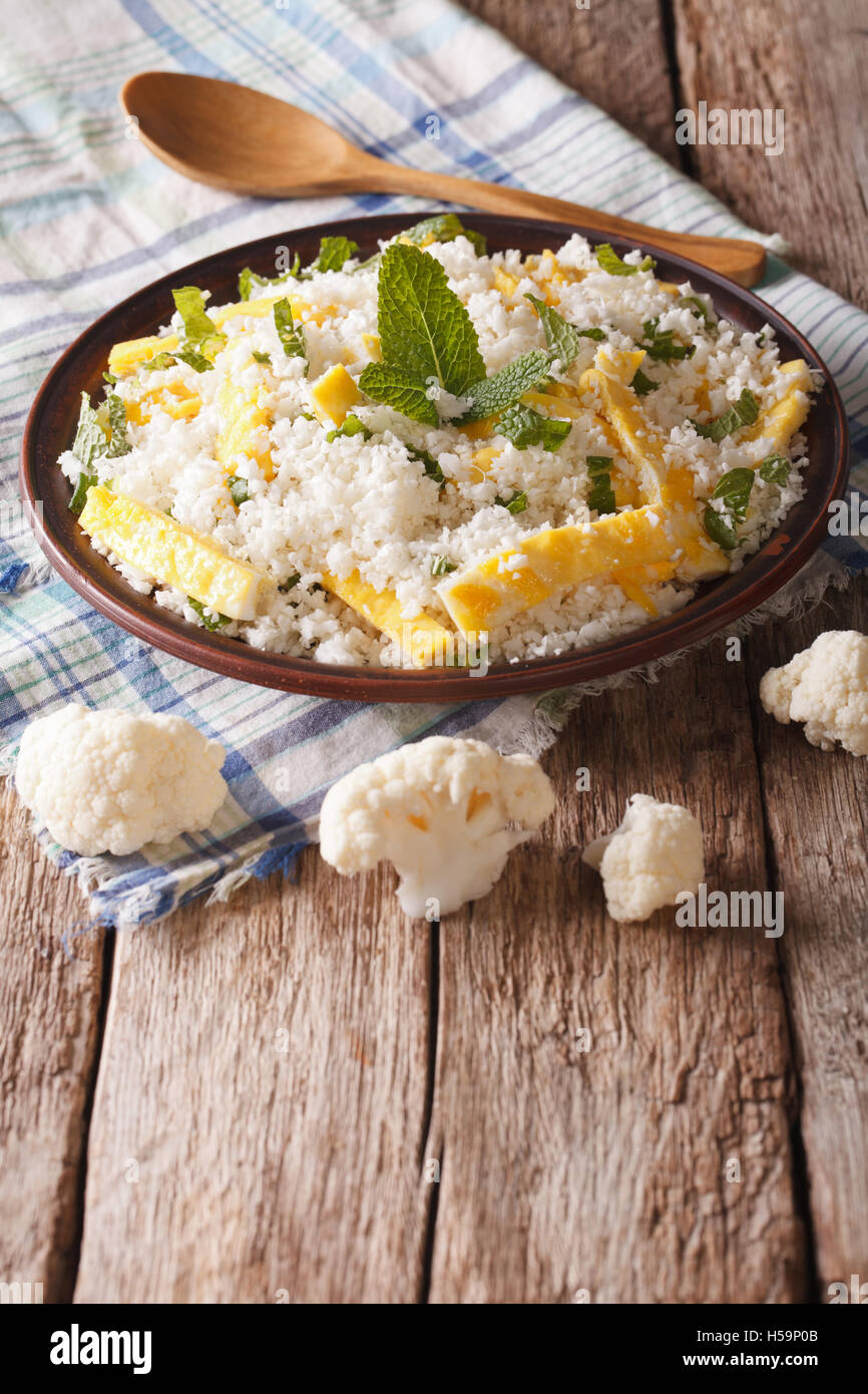 Diätetische Lebensmittel: Blumenkohl Reis mit Rührei und Kräuter Closeup auf einem Teller. Vertikal Stockbild