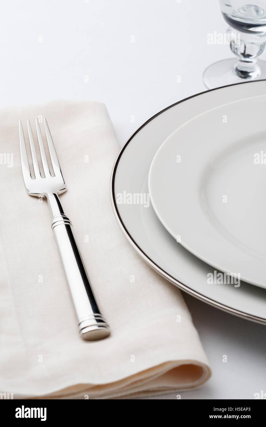 Feine Esstisch Gedeck mit hochwertigen klassischen Stil Weißware Geschirr, Leinen-Serviette und Besteck Gabel Stockbild
