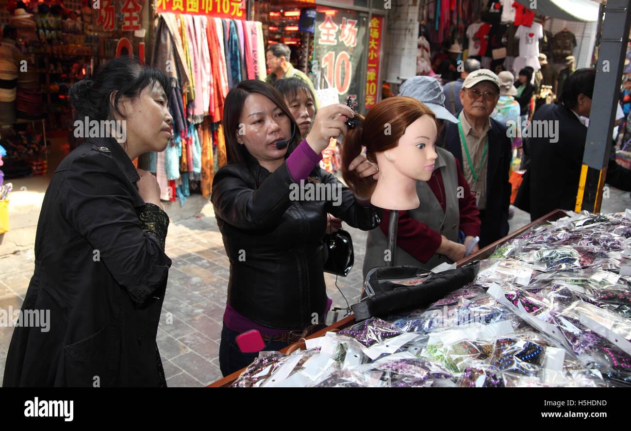 Eine Frau kämmt eine Schaufensterpuppe Perücke zu einem Galanterie, Gespräche über ein Mikrofon Stockbild