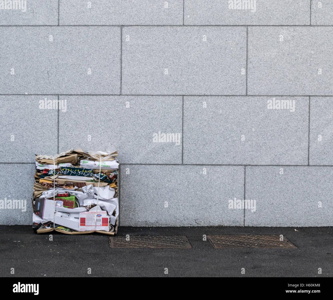 Abgeflacht, Papier und Pappe recycling sitzt gegen eine graue Steinmauer mit Kanalabdeckungen auf dem Weg Stockbild