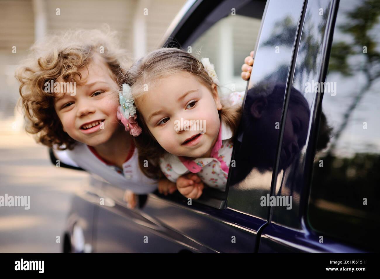 Kinder schauen aus einem Autofenster Stockfoto