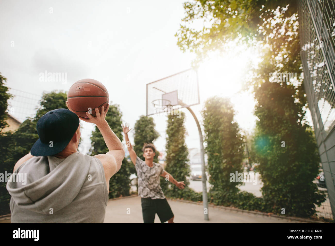 Streetball Spieler auf Platz Basketball zu spielen. Junger Kerl nehmen erschossen in den Korb mit Freund blockieren. Stockbild