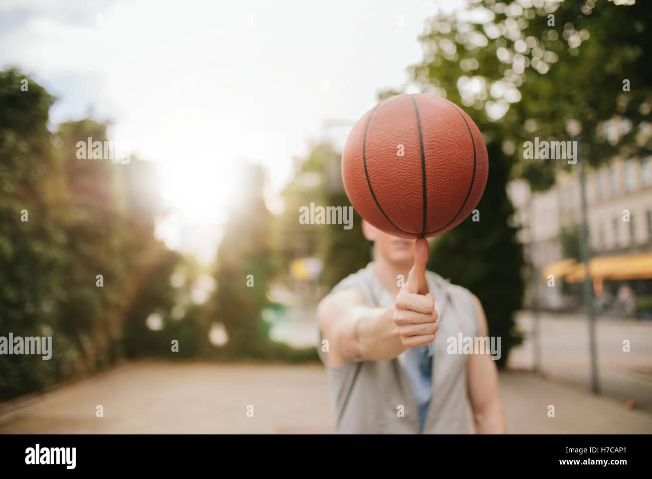 Mann Ausgleich Basketball auf seinem Daumen auf Freiplatz. Streetball Spieler den Ball drehen. Basketball im Vordergrund. Stockbild