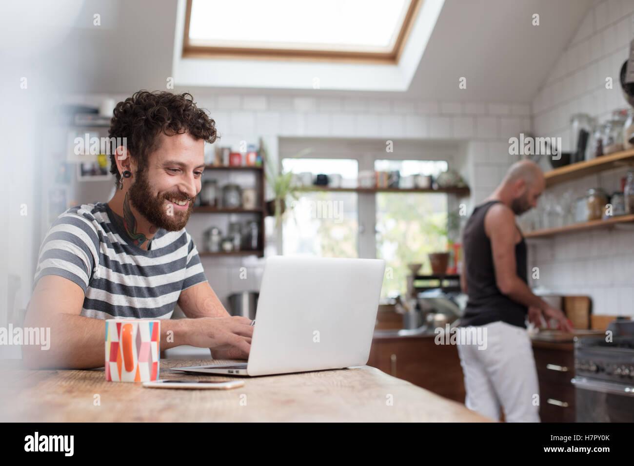 Gay paar mit Laptop und kochen in der Küche Stockbild