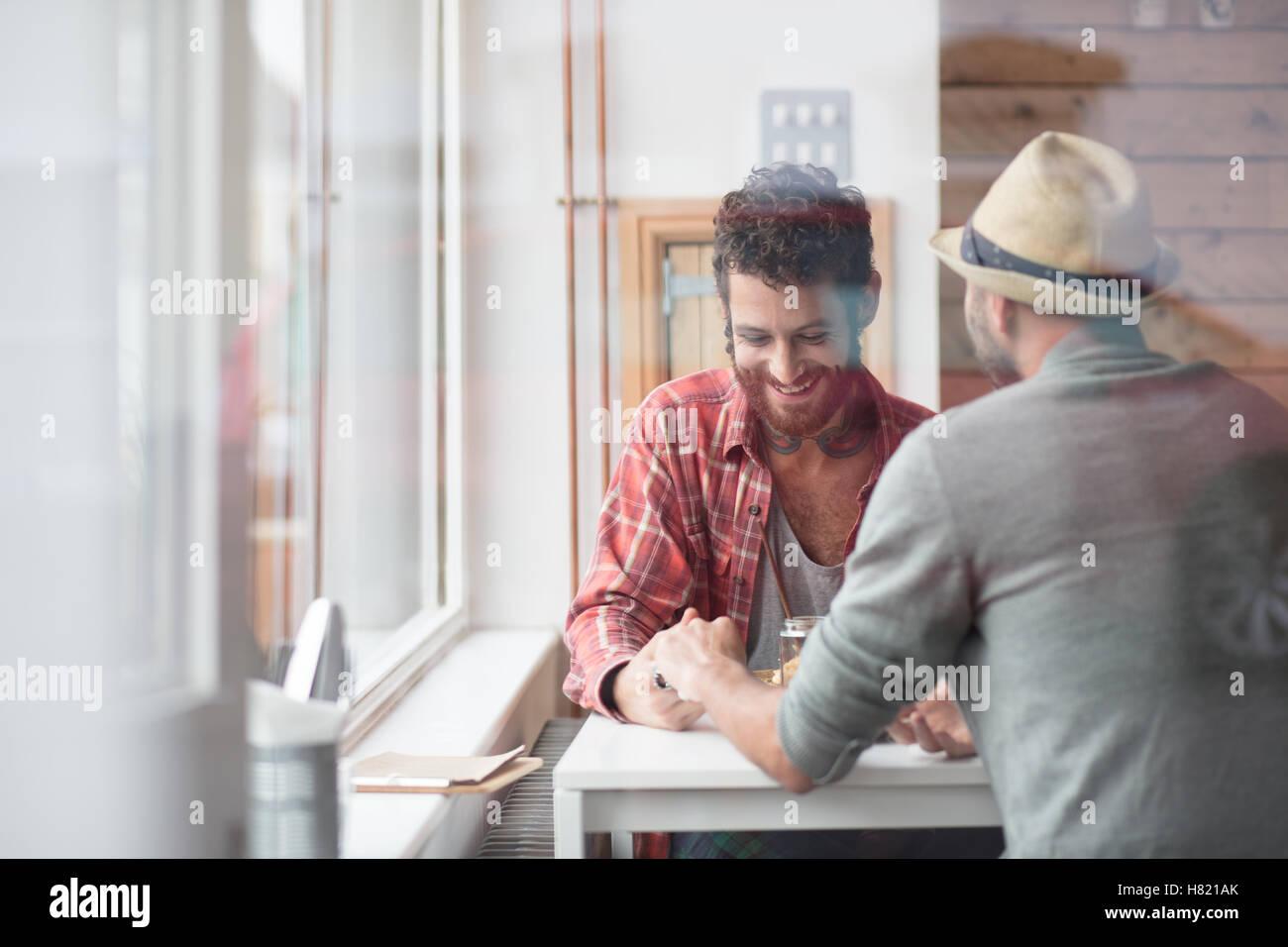 Gay paar saßen Hand in Hand im café Stockbild