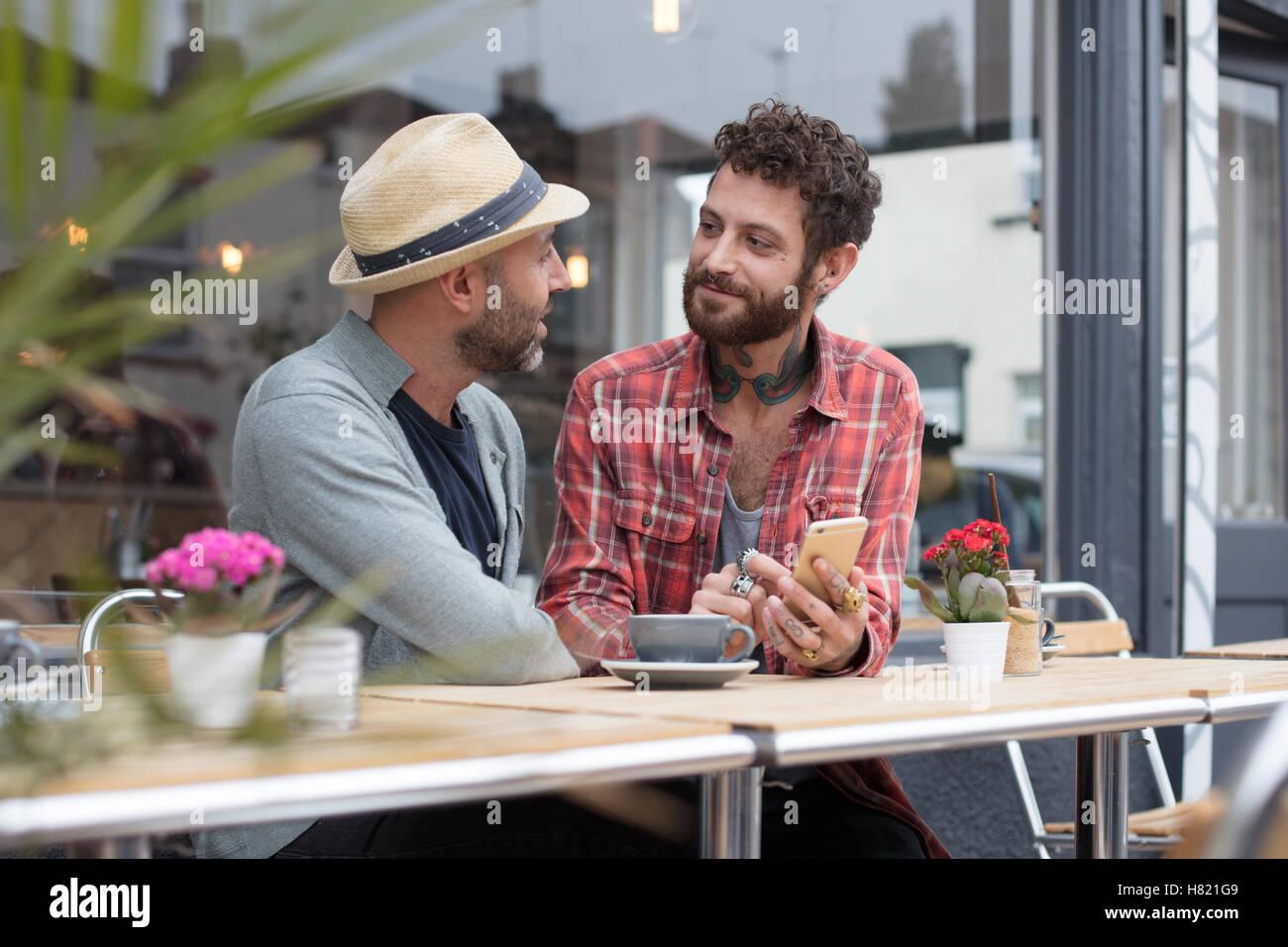 Gay paar Teilen Telefon im café Stockbild
