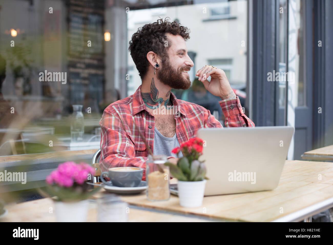 Junge tätowierte Hipster mit Laptop vor café Stockfoto