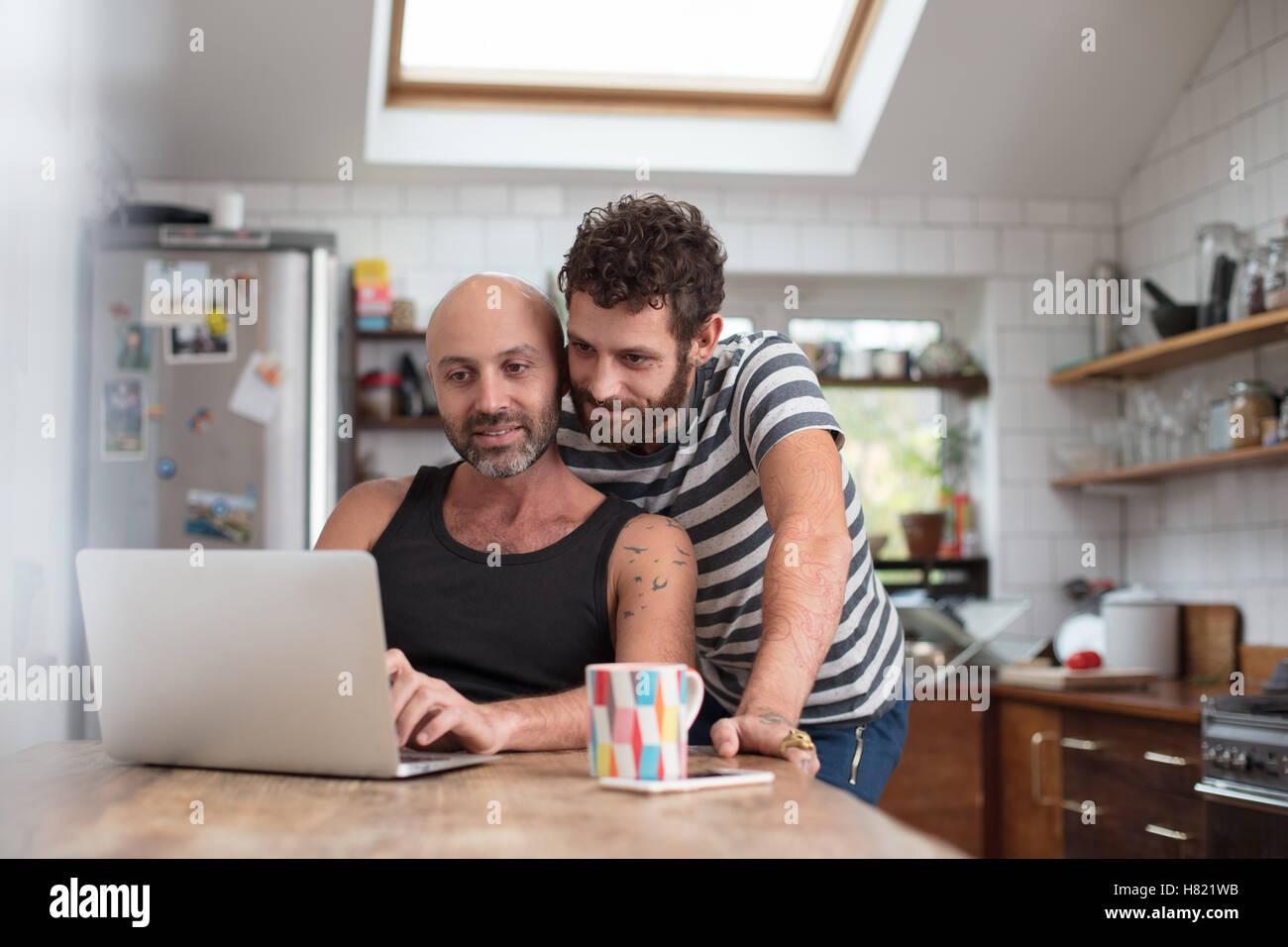 Gay paar mit Laptop in der Küche Stockbild