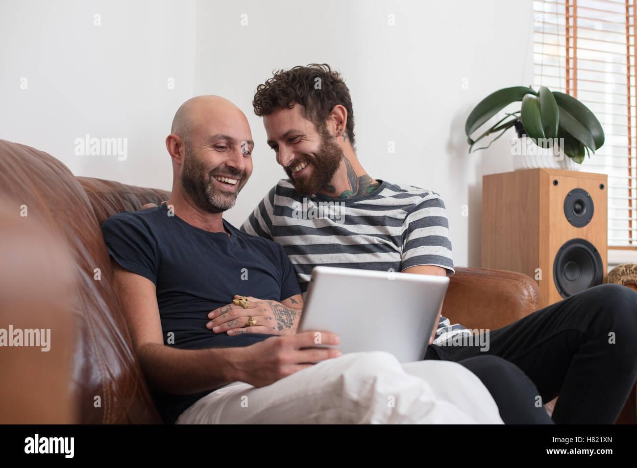 Gay paar saß auf Sofa, teilen Tablet kuscheln Stockbild