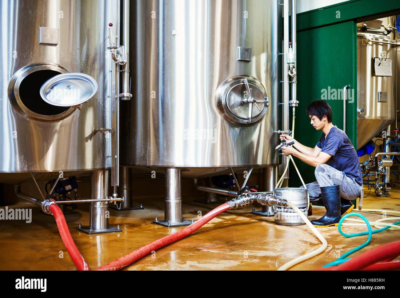 Mann arbeitet in einer Brauerei, kniet neben einem Metall Bier-Tank. Stockbild