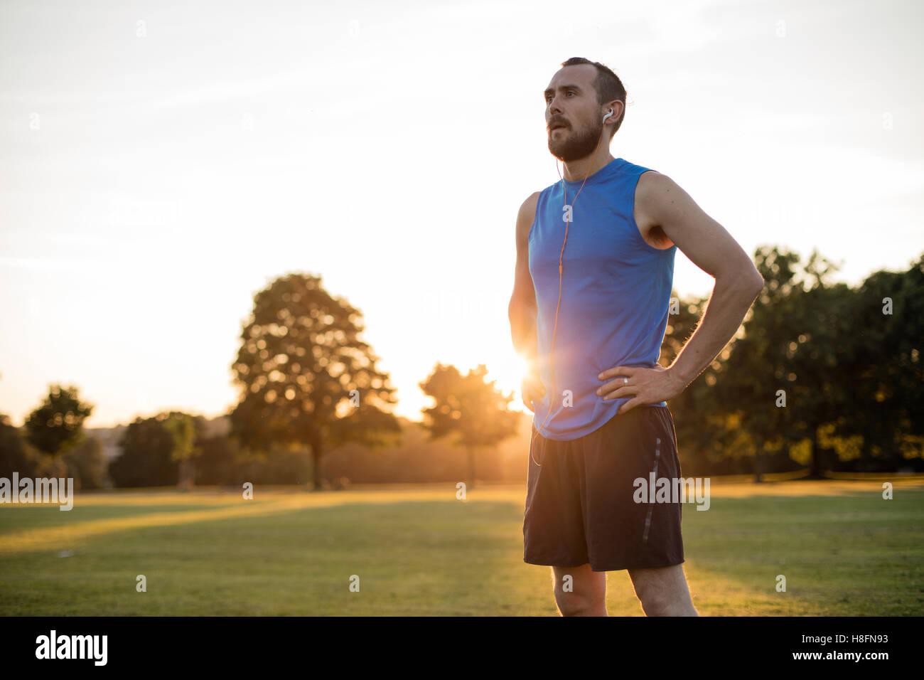 Junger sportlicher Mann, ruhen Sie sich nach einem Lauf im Park, während die Sonne untergeht Stockbild