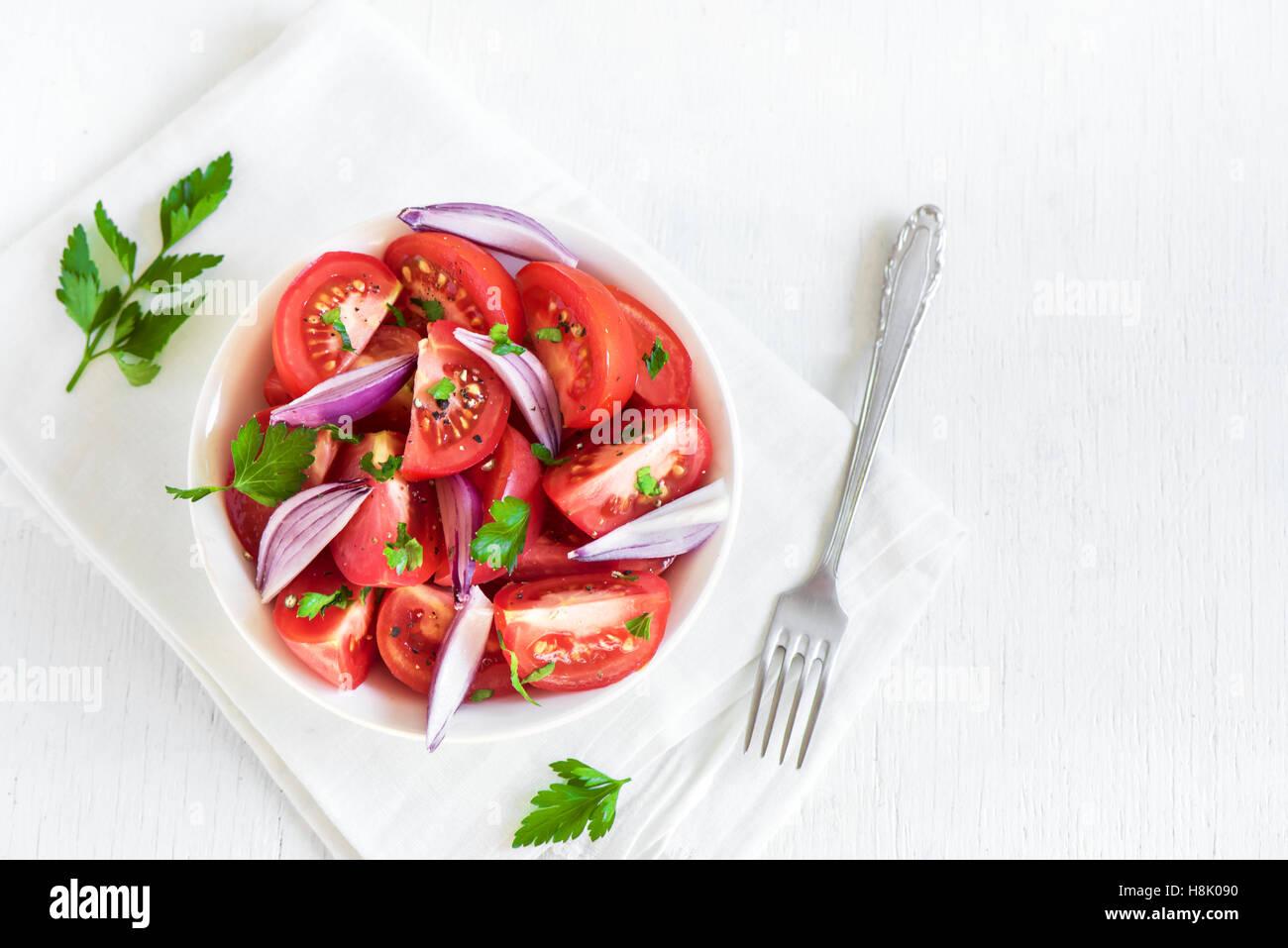 Tomatensalat mit Zwiebeln, Petersilie und Pfeffer in Schüssel - gesunde vegetarische vegane Lebensmittel Vorspeise Stockbild
