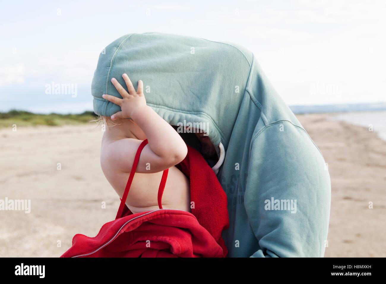Mädchen (2-3) versteckt im väterlichen hooded Hemd Stockbild