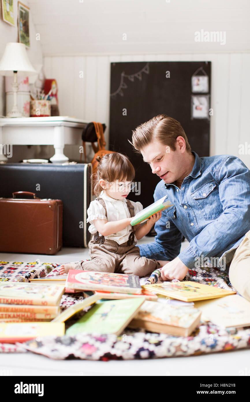 Vater mit Tochter (2-3)-Bilderbuch lesen Stockbild
