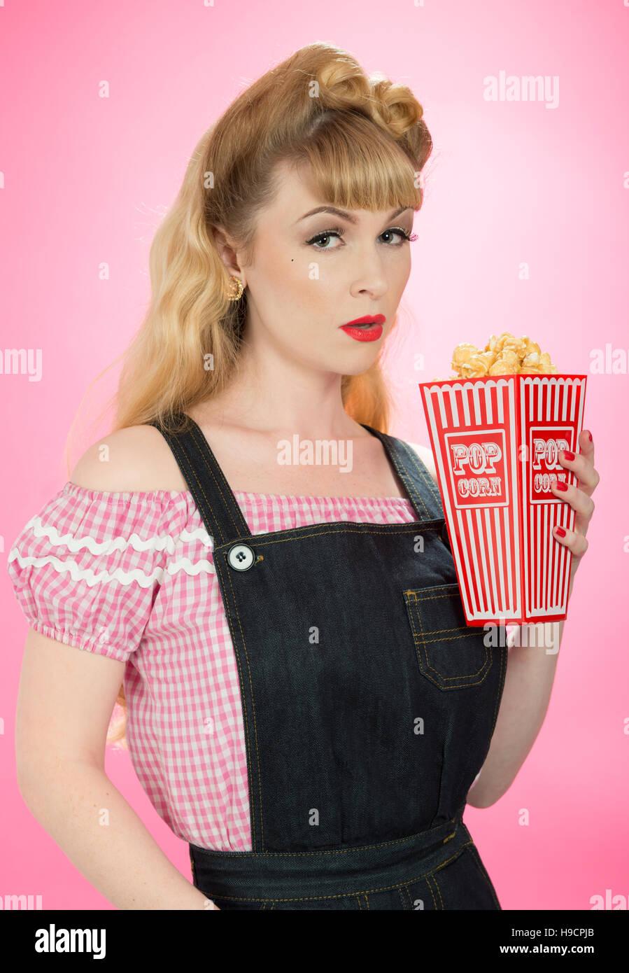 Pin-up Girl mit Karton auf Popcorn auf einem hellen rosa Hintergrund Stockbild