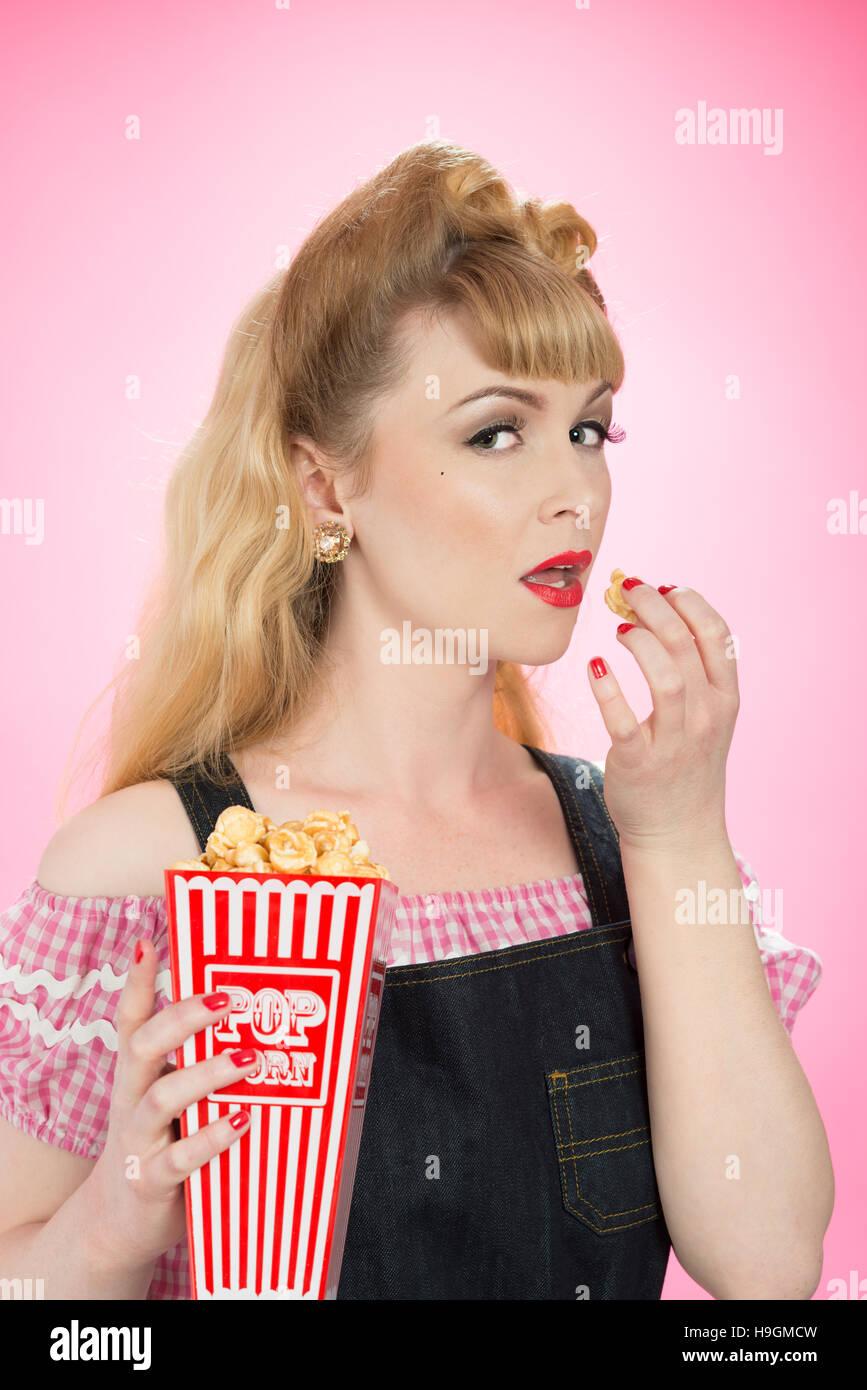 Pin-up Girl aus einem Karton Popcorn essen Stockbild