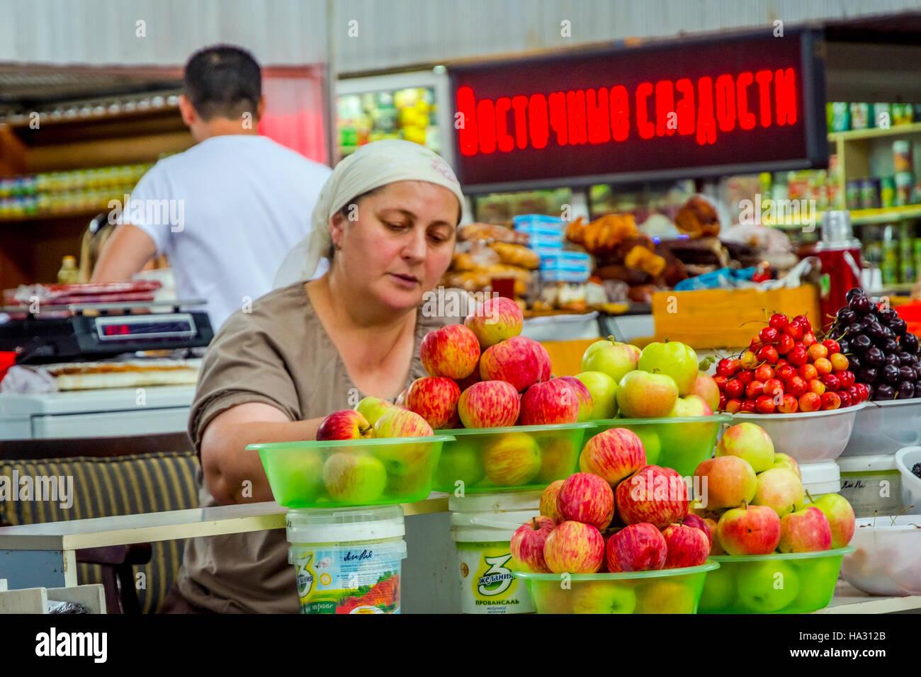 ALMATY, Kasachstan - 15 Juli: Ältere Frau Äpfel auf grüne Basar zu verkaufen. Juli 2016Stockfoto