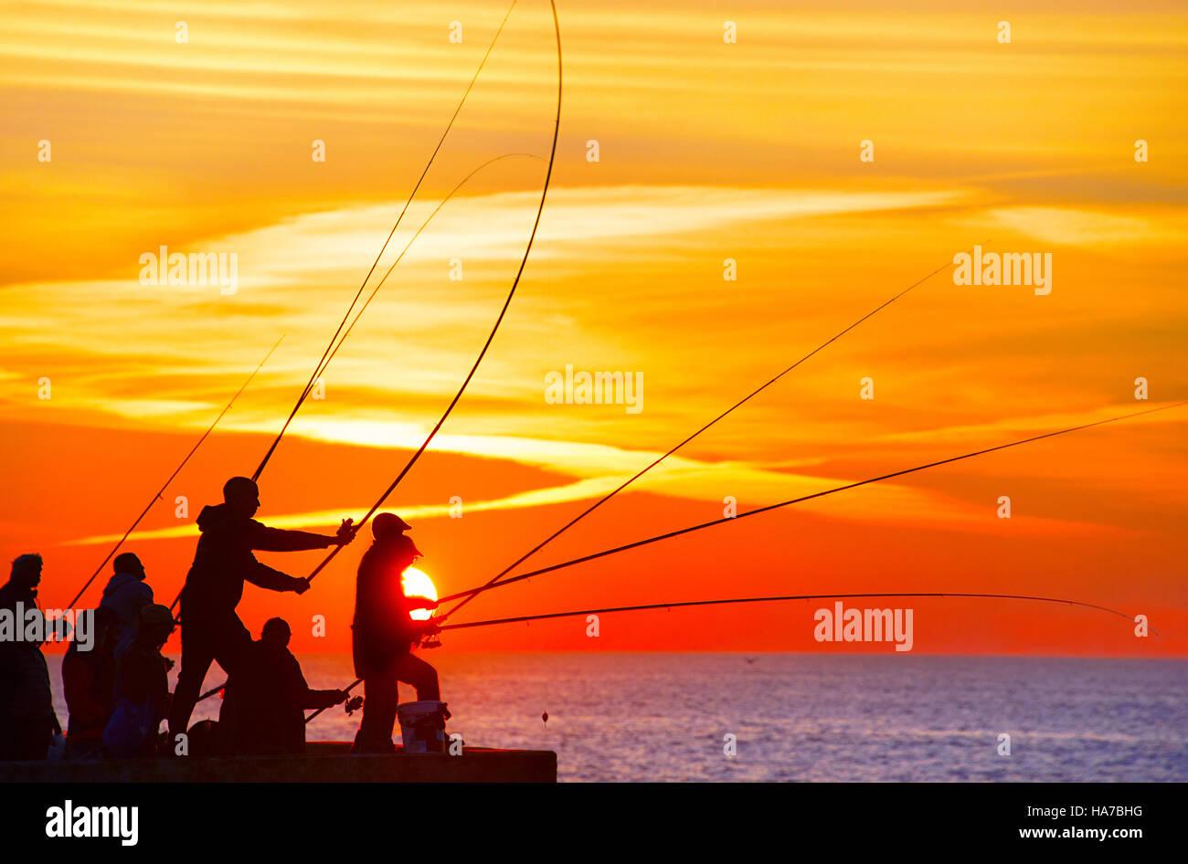 Gruppe von Fischer auf einem Pier bei Sonnenuntergang. Porto, Portugal Stockfoto