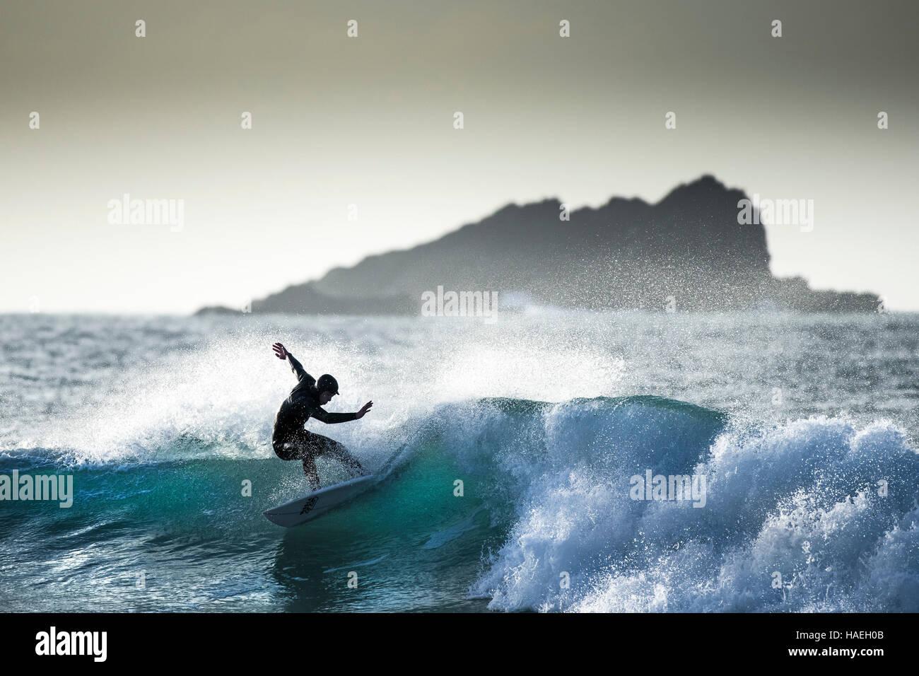 Ein Surfer in einer spektakulären Aktion auf den Fistral in Newquay, Cornwall, England.de. Stockbild