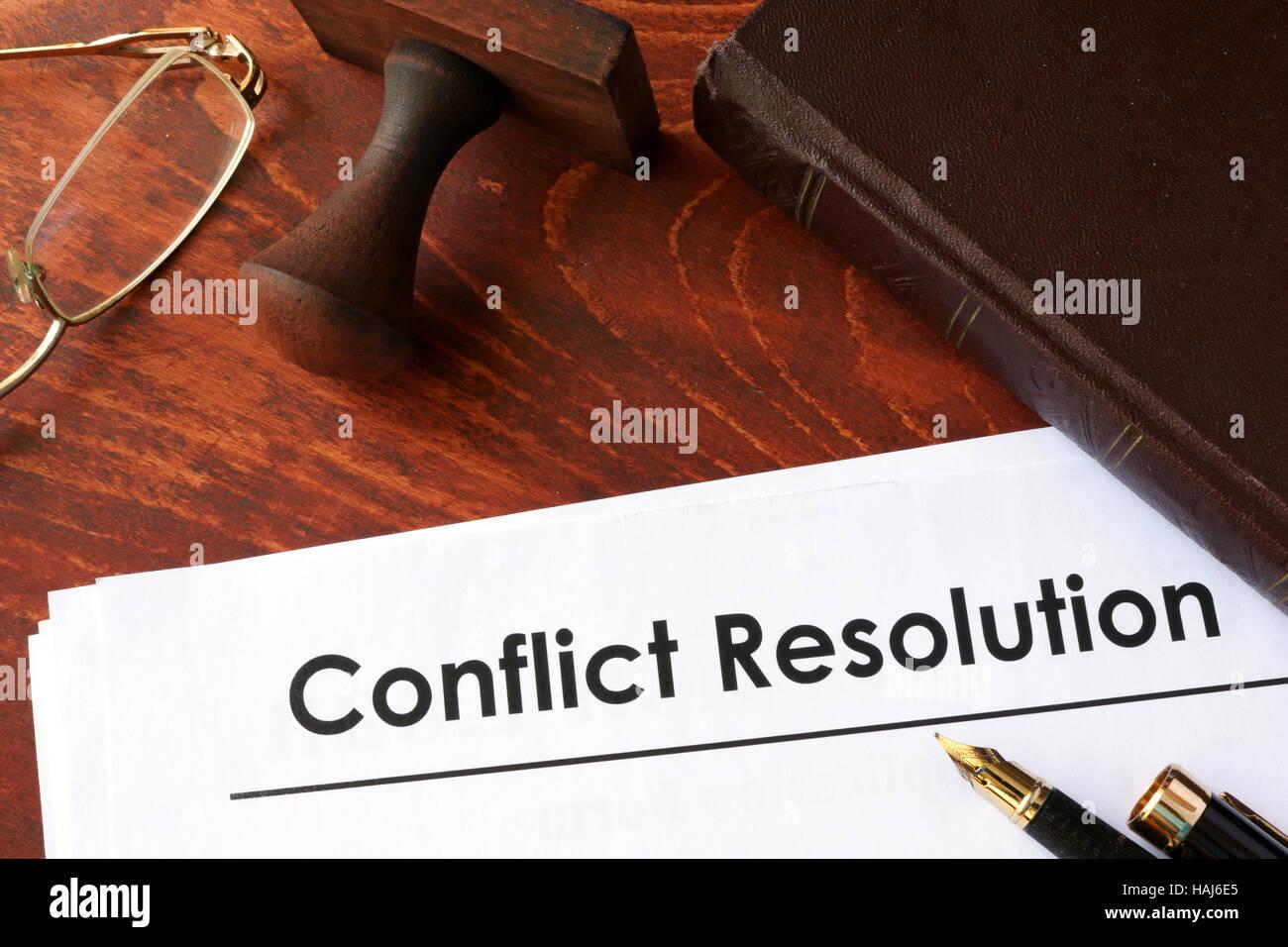 Papiere mit Titel Konfliktlösung auf einem Tisch. Stockbild