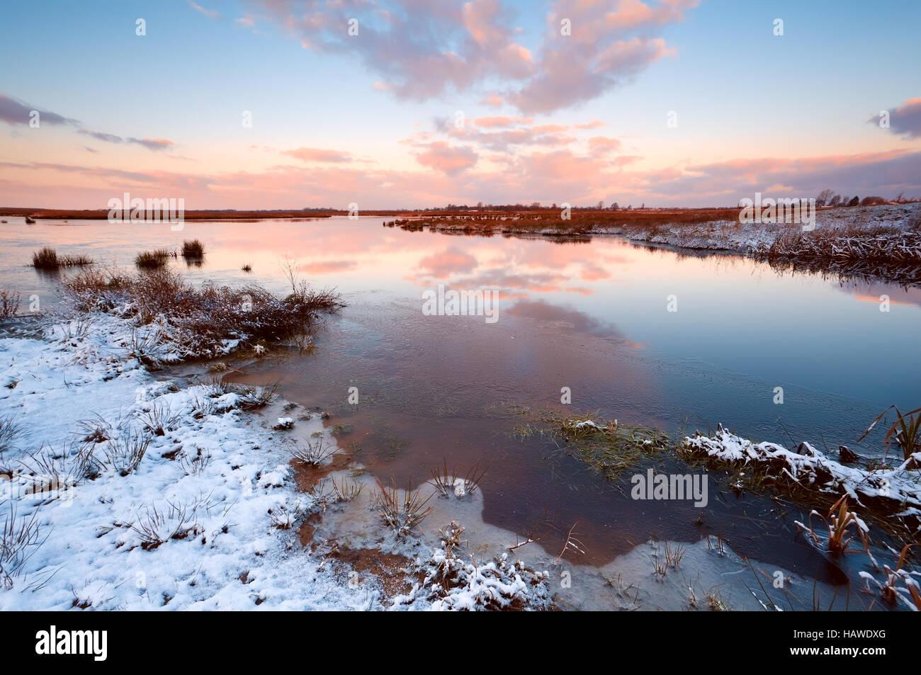 Sunrsie über Fluss im winter Stockbild