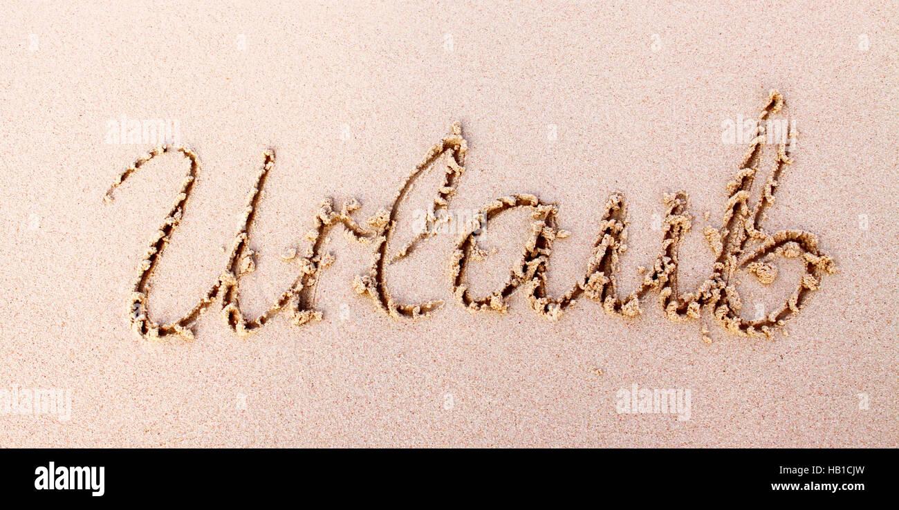Wort-Urlaub in Sand geschrieben. Stockbild