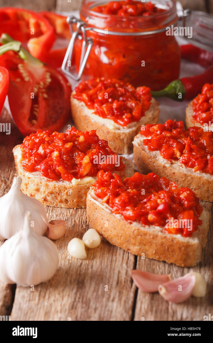 Selektiven Fokus auf Ajvar auf Vollkorn Brot Closeup auf dem Tisch. Vertikal Stockbild