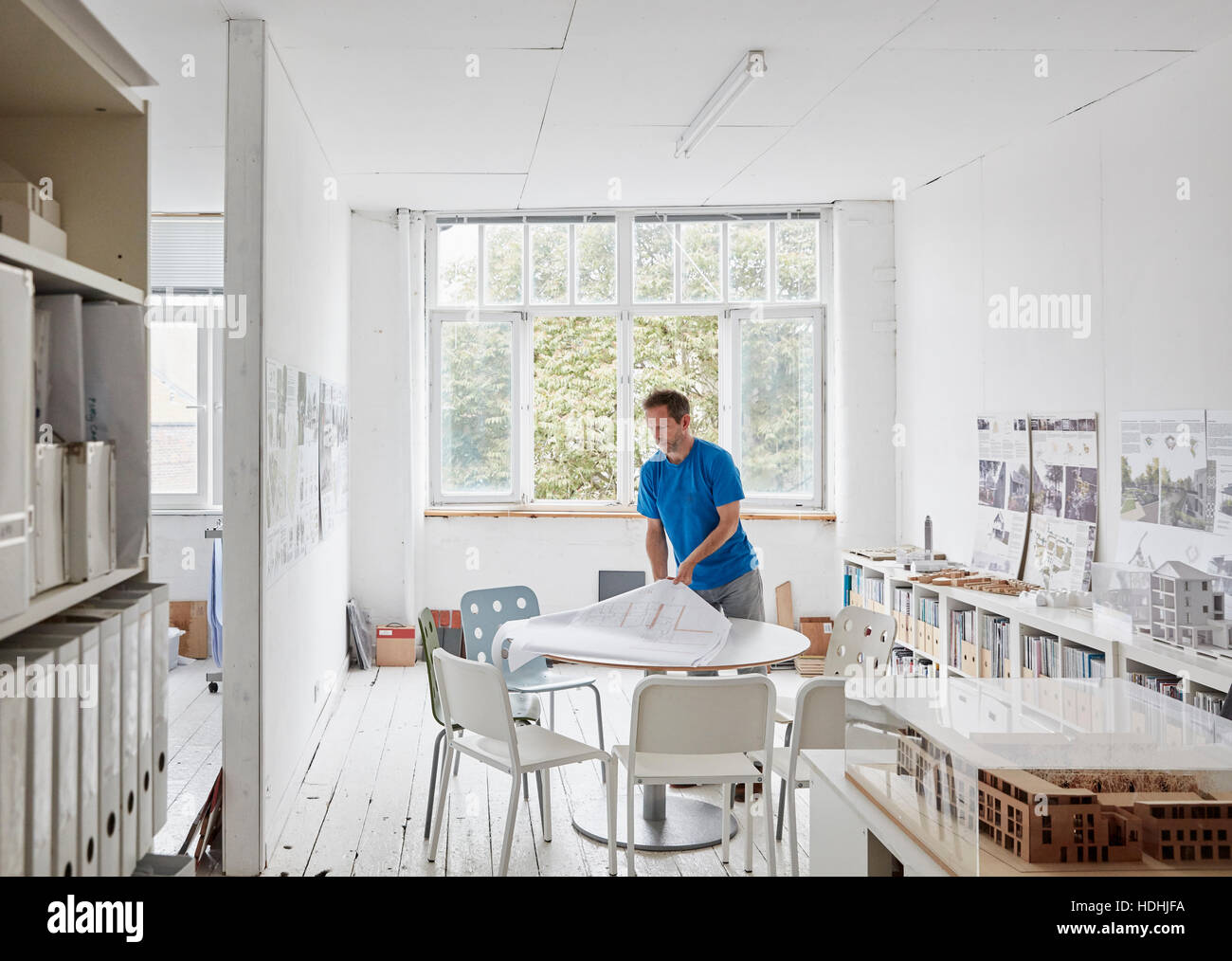 Ein modernes Büro. Ein Mann betrachtet man Pläne an einem Tisch, Bauzeichnungen. Gebäudemodelle in Stockbild
