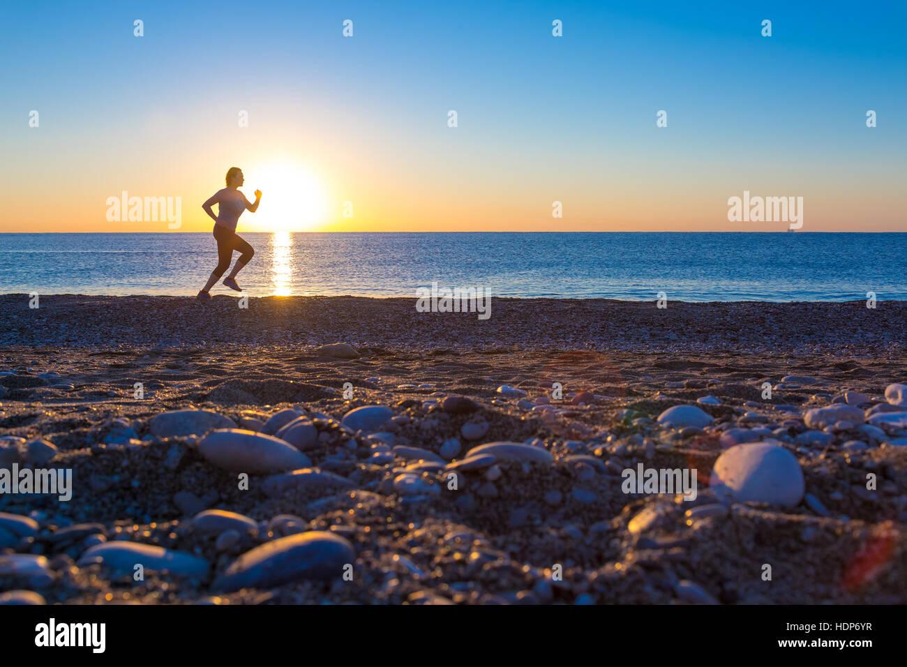 Silhouette der Sportlerin am Ocean Beach bei Sonnenaufgang Stockfoto