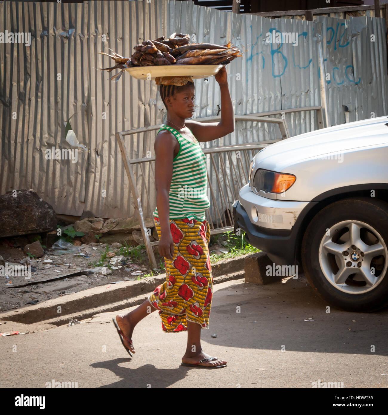 Frau trägt gebratenen Fisch auf dem Kopf Stockbild