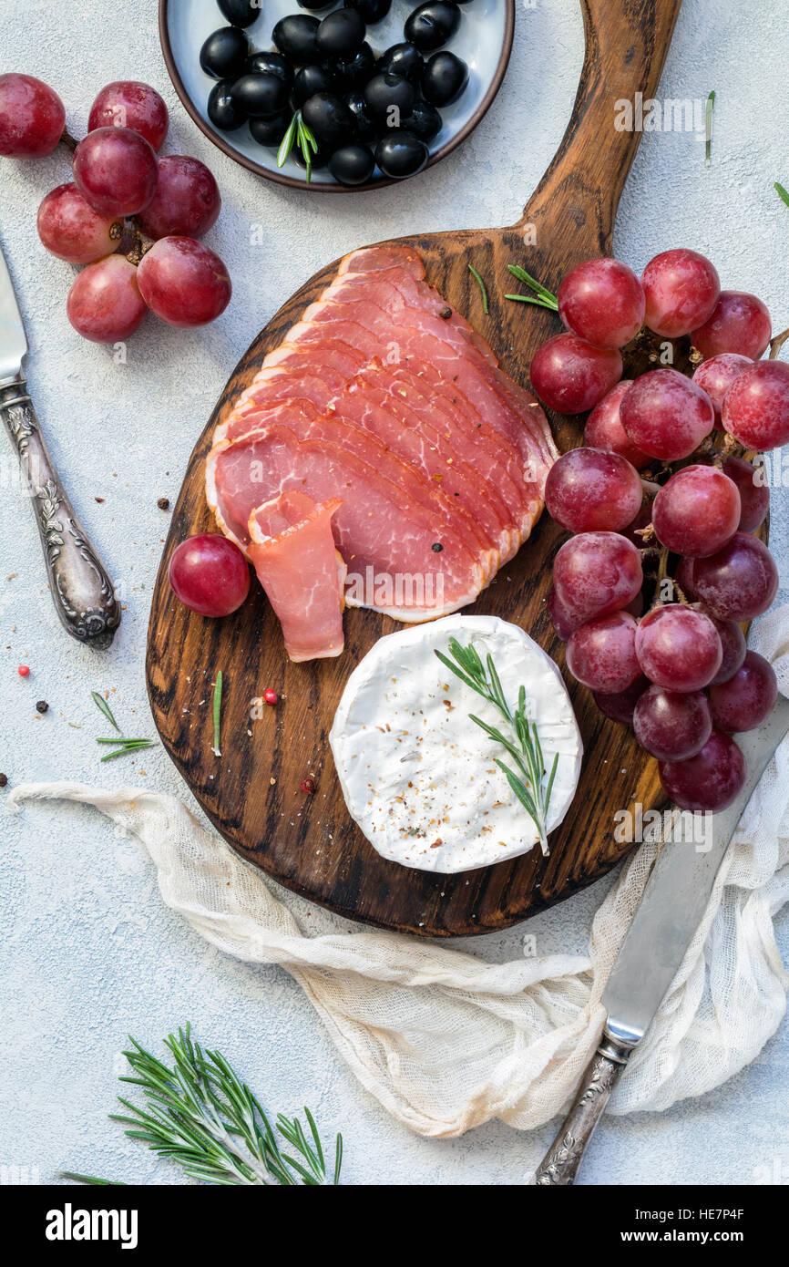 Vorspeise-Teller mit Fleisch, Trauben, Käse und Oliven. Antipasti oder Tapas-Konzept. Ansicht von oben Stockbild