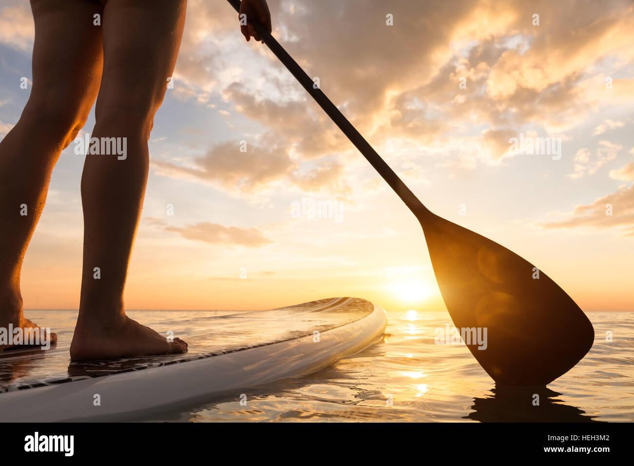 Paddle boarding auf einem ruhigen See mit warmen Sommerfarben Sonnenuntergang, Nahaufnahme Beine aufstehen Stockfoto