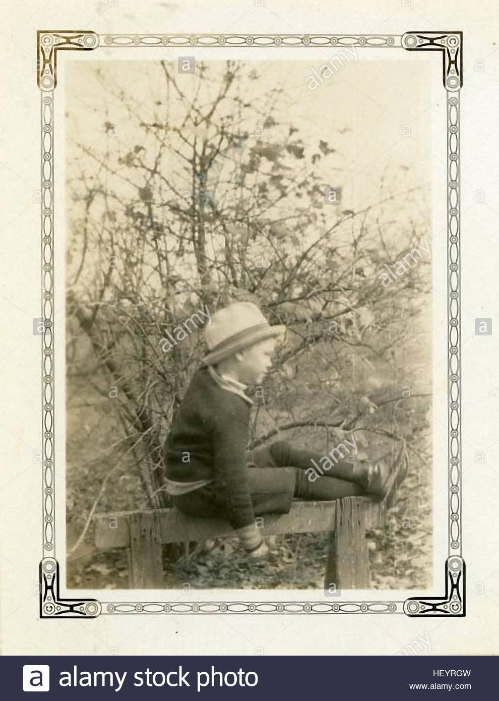 entzückende junge sitzt auf der Kante der Char auf den Vintage-Fotografie aus den 30er Jahren Stockbild