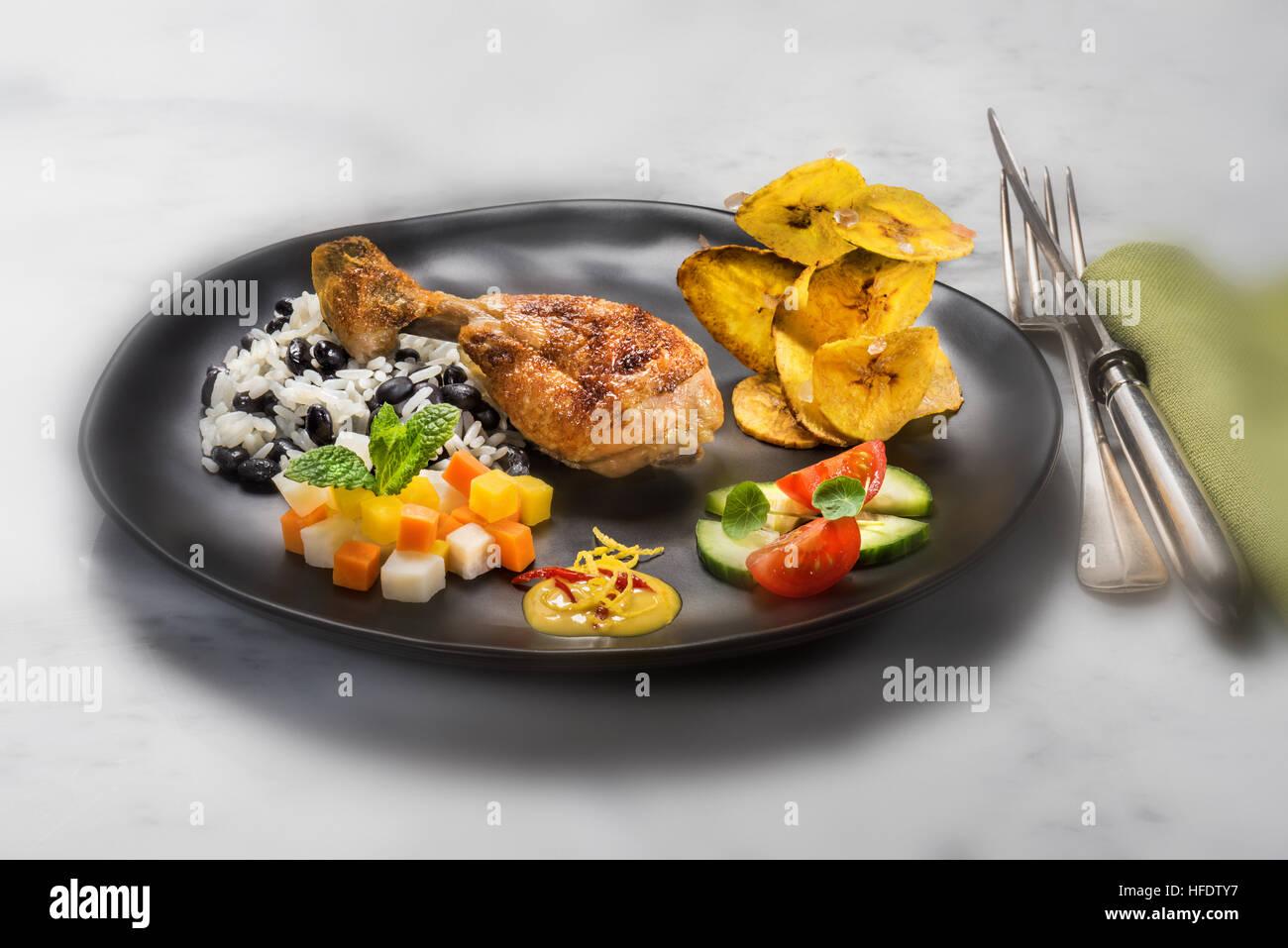 Typische kubanische Speisen, Huhn, Reis mit schwarzen Bohnen, gebratene Bananenchips, Salat und Gemüse. KUBA. Stockbild