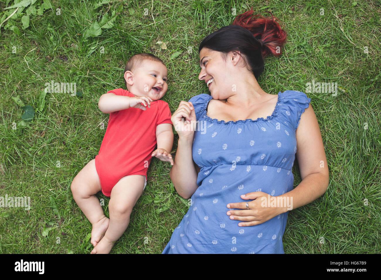 Overhead Schuss einer Mutter mit ihrem Baby Sohn auf dem Rasen kleben Stockbild