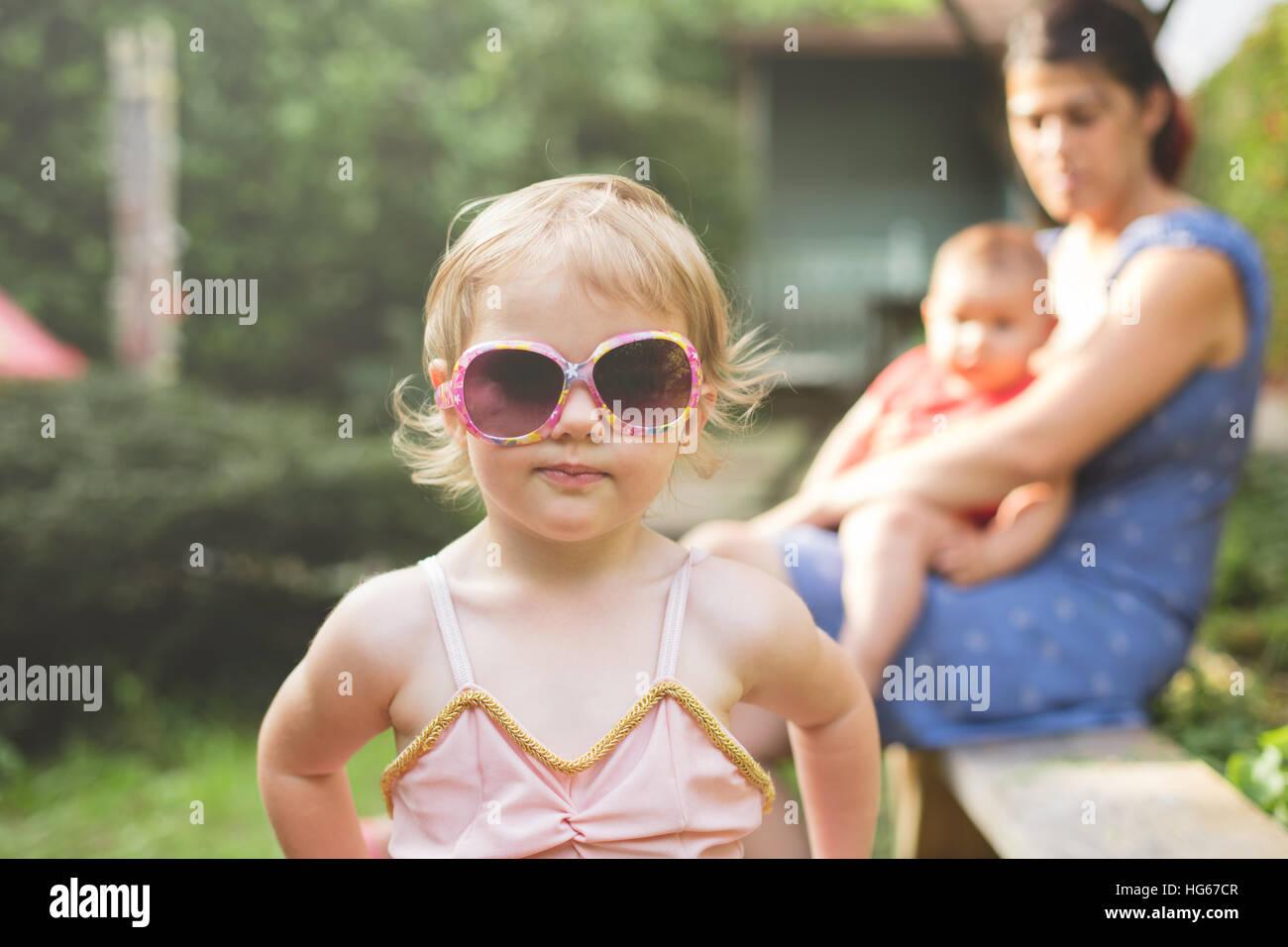 Porträt einer jungen Tochter, die ihre Mütter Sonnenbrille im Garten hautnah Stockbild
