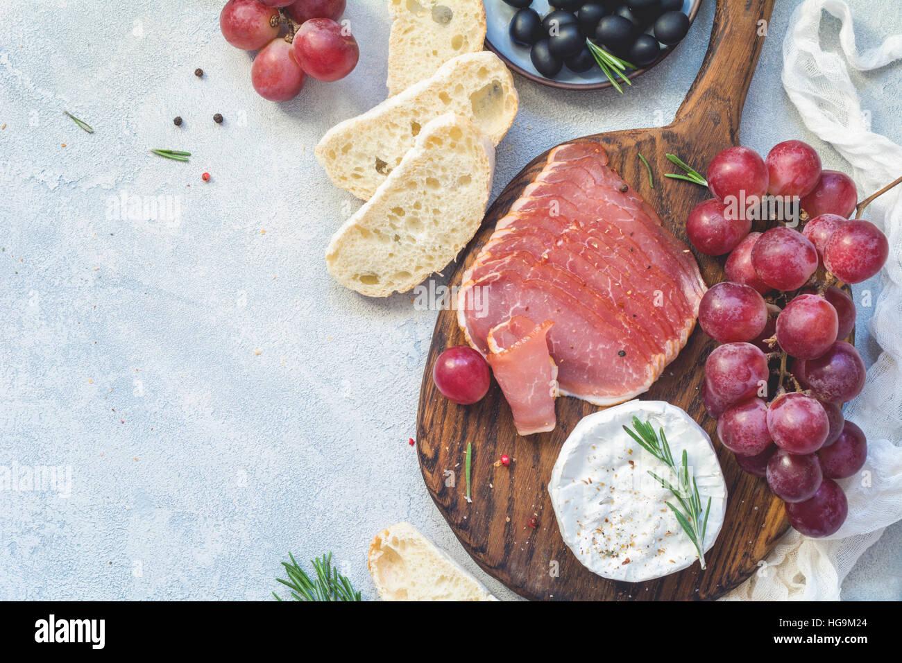Vorspeise-Teller mit frischem Baguette, Wurst, Trauben, Käse und Oliven. Antipasti oder Tapas-Konzept. Ansicht Stockbild