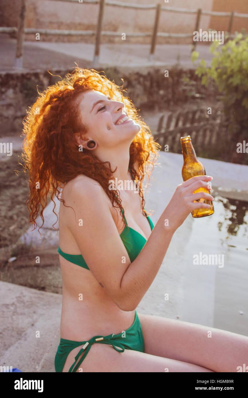 Junge rothaarige Frau an ein Sommerfest mit einer Bierflasche Stockbild
