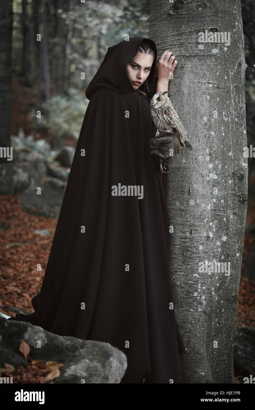Wald-Halter mit schwarzen Mantel und graue Eule. Fantasie und Legende Stockbild