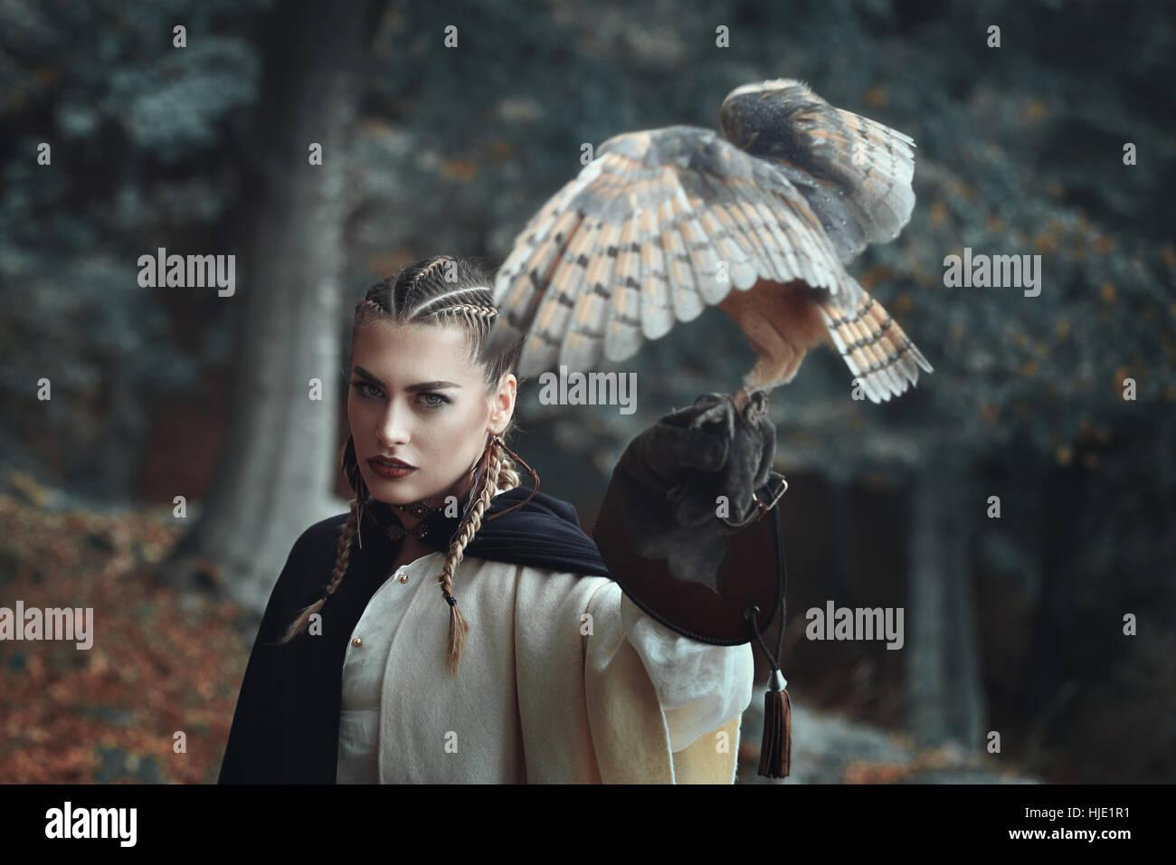 Schöne Dame in surrealen Wald mit einer Eule. Fantasie und Falknerei Stockbild